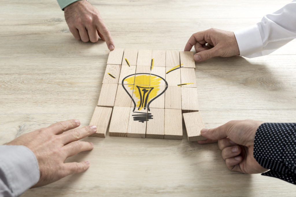 Four businessmen holding pieces of a wooden bricks bearing the image of a light bulb conceptual of business strategy, creativity or teamwork.