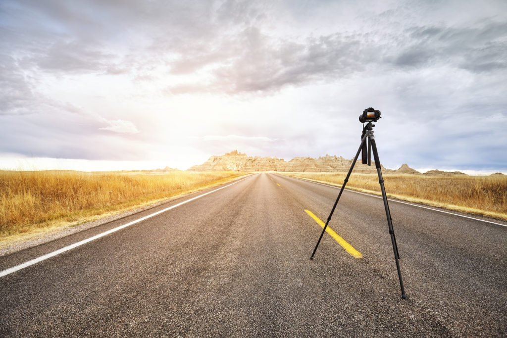 Professional photo camera on tripod on an empty road at sunset, focus on the camera, travel or work concept, Badlands National Park, South Dakota, USA.