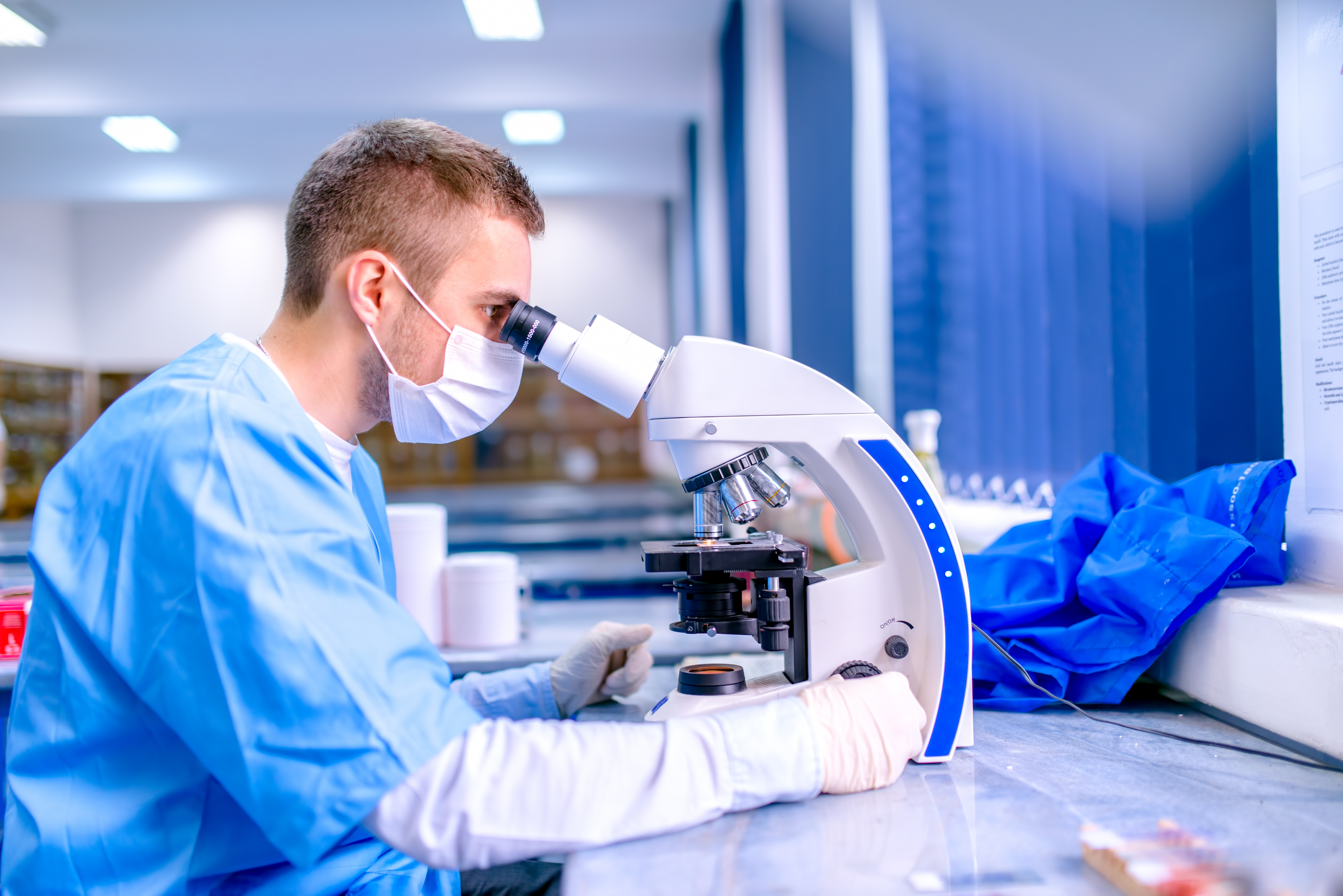Scientist working in chemistry laboratory, examining samples at microscop