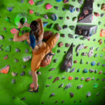 young-woman-bouldering-in-climbing-gym-PMDGMN4